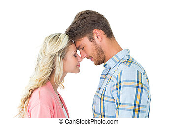 Attractive couple standing touching heads on white...