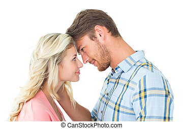Attractive couple smiling at each other on white background