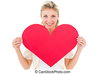Attractive young blonde showing red heart on white...