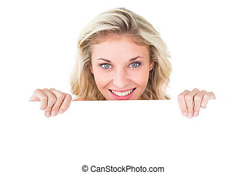 Pretty young blonde showing poster on white background
