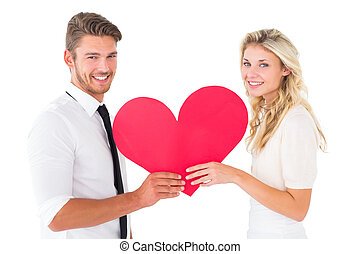 Attractive young couple holding red heart on white...