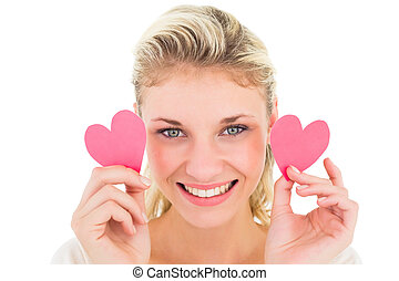 Attractive young blonde holding little hearts on white...