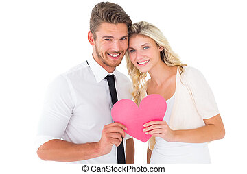 Attractive young couple holding pink heart on white...