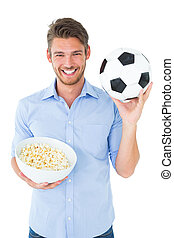 Handsome young man holding ball and popcorn on white...