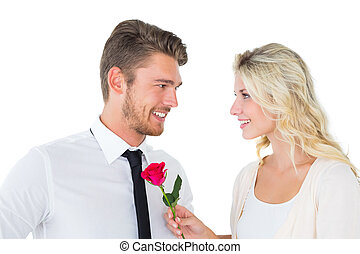 Handsome man smiling at girlfriend holding a rose