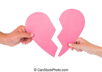 Couple holding two halves of broken heart on white...