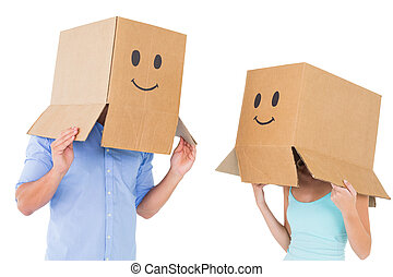 Couple wearing emoticon face boxes on their heads on white...