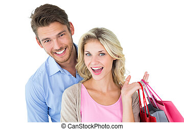 Attractive young couple holding shopping bags on white...