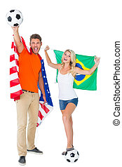 Excited football fan couple holding usa and brazils flag
