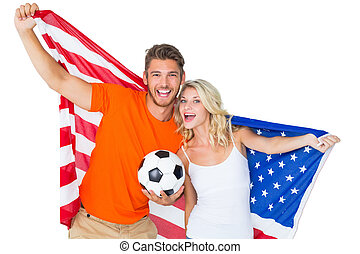 Excited football fan couple holding usa flag on white...