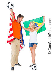 Excited football fan couple holding usa and brazils flag on...