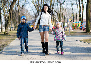 3 people beautiful mom walking in the park with her son and daughter happy smiling & looking at camera on spring or autumn outdoors background