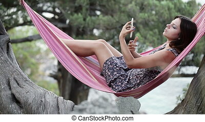Girl in hammock smartphone self - Lying in hammock girl...