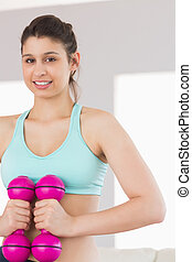 Fit brunette holding pink dumbbells at home in the living...