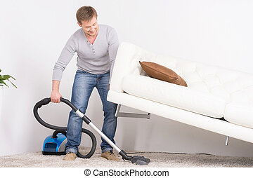 man does house work with vacuum cleaner. Men lifted sofa in...