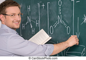 confident young teacher and classic chalkboard background....