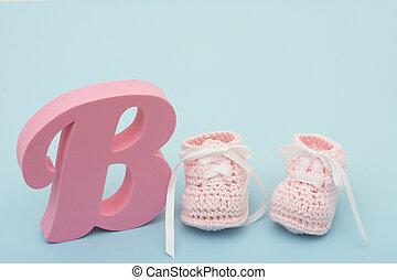 Pink Baby Booties - A large pink B with baby booties on a...