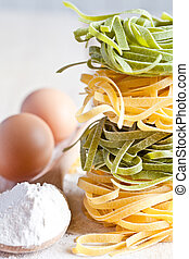 italian pasta tagliatelli, flour and eggs closeup on wooden...