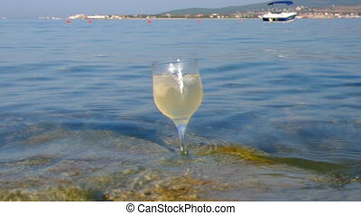 Glass of white wine by the coast.on the rocks, washed by the...