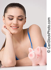 Happy female looking at table with piggy bank. close up shot...