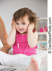 Cute little girl listening to music on bed - Portrait of a...