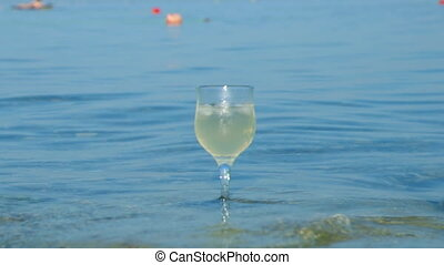 Glass of white wine by the coaston the rocks, washed by the...