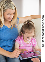 Mother and daughter using digital tablet on couch - Mother...