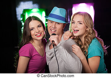 Group of three friends singing with microphone. man with...