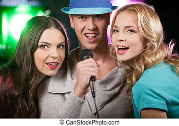 Group of three friends singing with microphone closeup of...