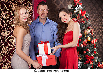 wo happy women and man holding gift boxes smiling brunette...