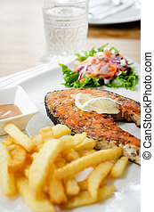 grilled salmon steak served with salad, chips,