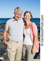 Happy casual couple smiling at camera by the coast