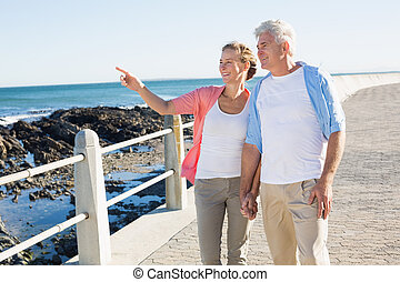 Happy casual couple walking by the coast on a sunny day