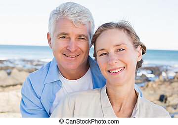 Happy casual couple by the coast on a sunny day