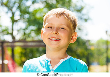 Little boy portrait with big smile outside