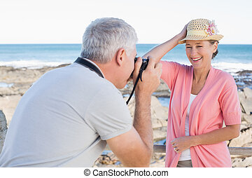 Happy casual man taking a photo of partner by the sea on a...