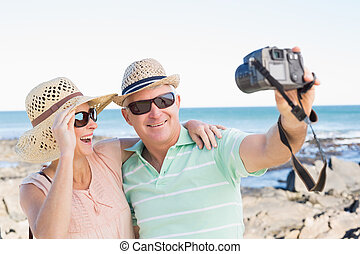 Happy casual couple taking a selfie by the coast on a sunny...