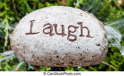Rock inscribed with word Laugh.