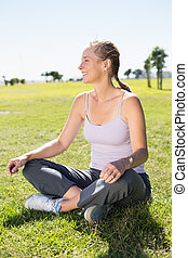 Fit mature woman sitting in lotus pose on the grass on a...