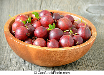 Fresh gooseberries in bowl on wooden table