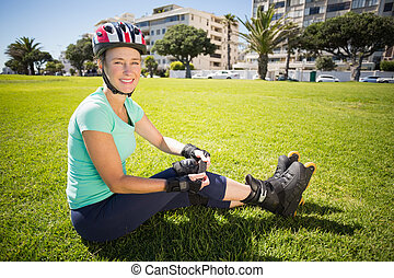 Fit mature woman in roller blades on the grass on a sunny...