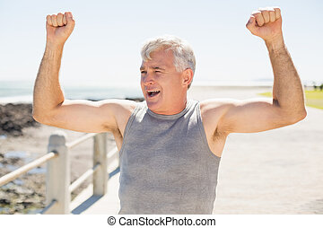 Fit mature man cheering on the pier on a sunny day