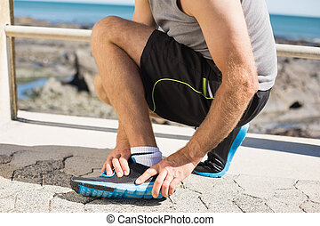 Fit man gripping his injured ankle