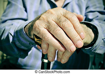 old man - closeup of the hands of an old man with a walking...