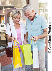 Happy mature couple looking at their shopping purchases on a...