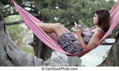 Girl in hammock smartphone self - Lying in hammock girl...