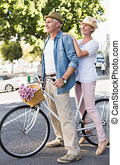 Happy mature couple going for a bike ride in the city on a...