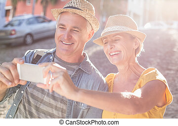 Happy mature couple taking a selfie together in the city on...