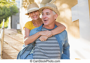Happy mature couple having fun in the city on a sunny day