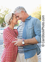 Happy mature couple hugging in the city on a sunny day